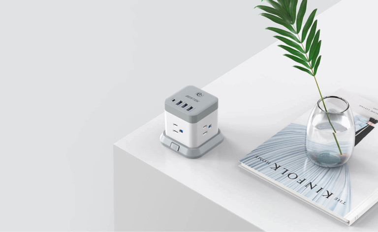 A white and gray useful office gadgets power cube on the corner of a white desk.