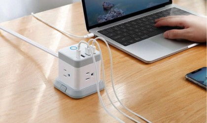 A gray and white useful office gadgets power cube on a wood desk with cords plugged into it, next to a person working on a laptop.