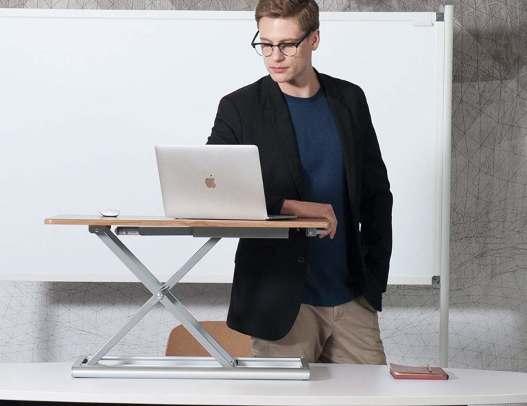 A man standing at a useful office gadgets standing desk with a laptop on top of it.