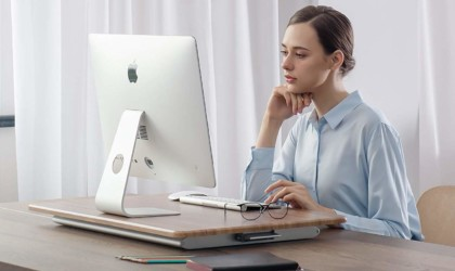 A woman sitting at a desk with a useful office gadgets standing desk converter on it.