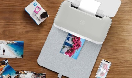 An open useful office gadgets printer, printing pictures.