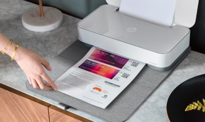 A small gray useful office gadgets printer that is printing out a page of colorful coupons.