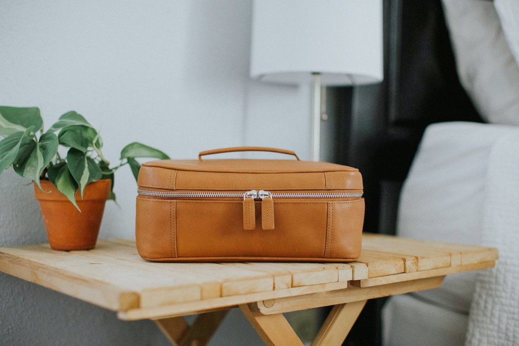 Zipped leather toiletry bag on a small table