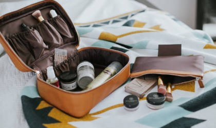 Opened leather toiletry bag with toiletries