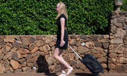 Woman walking with rolling suitcase behind her