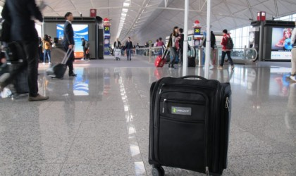 Rolling suitcase on its own in a busy airport terminal