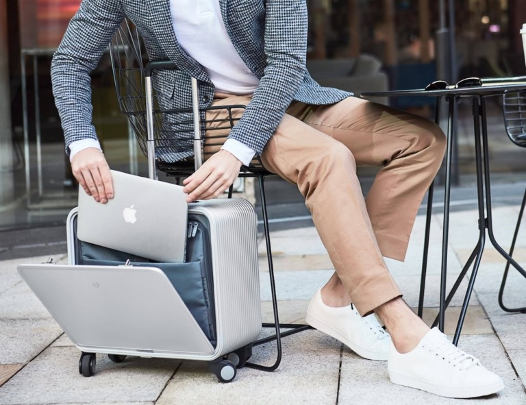 Person reaching into carry on bag for laptop