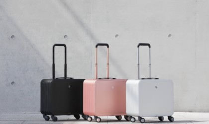 Three aluminum carry on bags arranged in a line