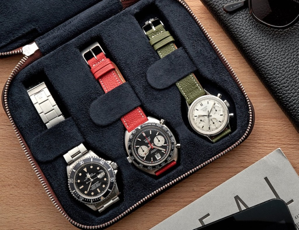 Three watches strapped into a watch travel case