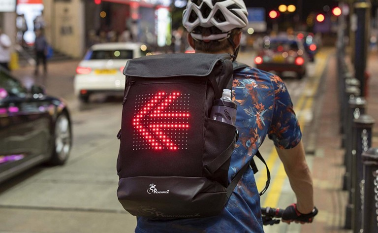 A person is wearing a backpack while they are on a bike and the backpack has a lighted arrow on the back.