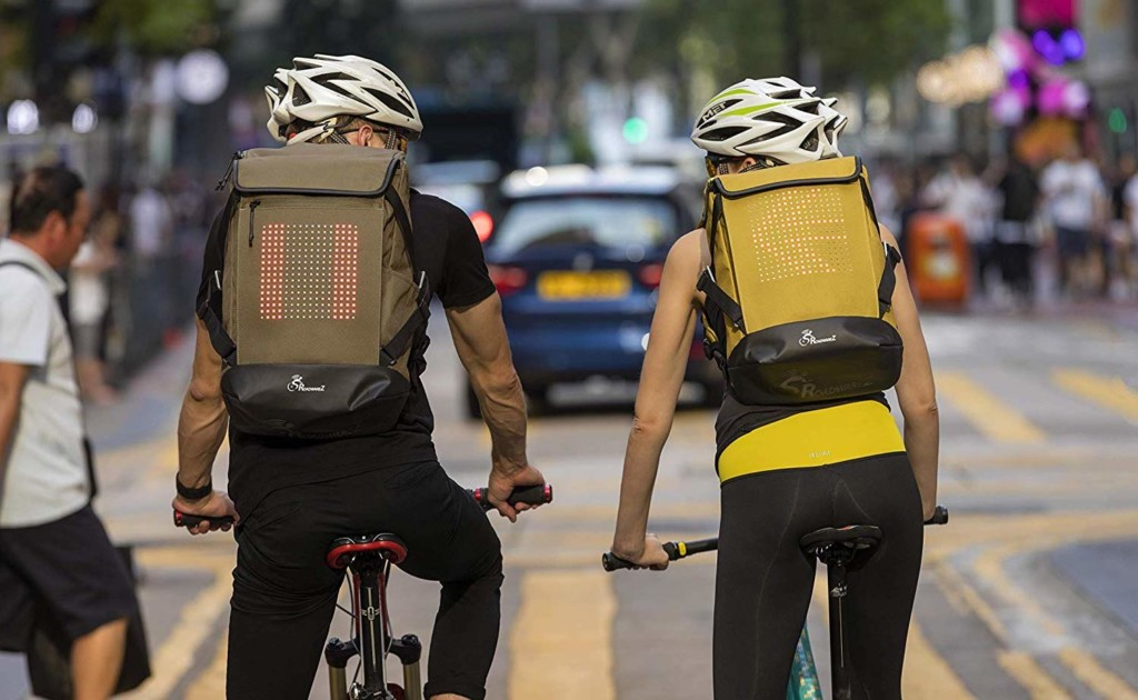 Two people are riding bicycles and they are wearing backpacks with light-up arrows on them.