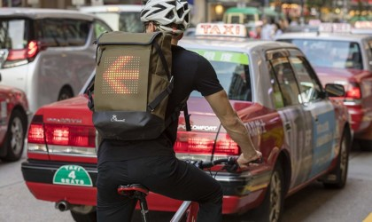 A man is riding a bicycle in traffic and he is a wearing a backpack with a light-up arrow on it.