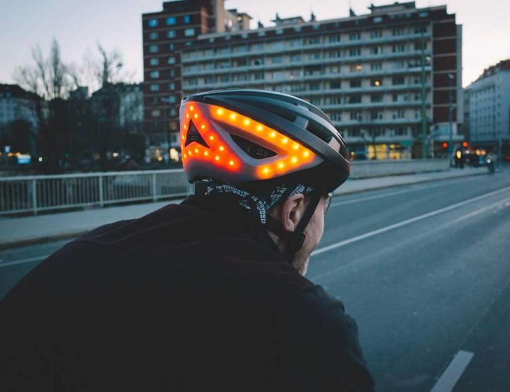 A rear view of a man wearing a black helmet with orange lights on it.