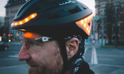 A side view of a man wearing a black bike helmet with orange lights on the front and back.