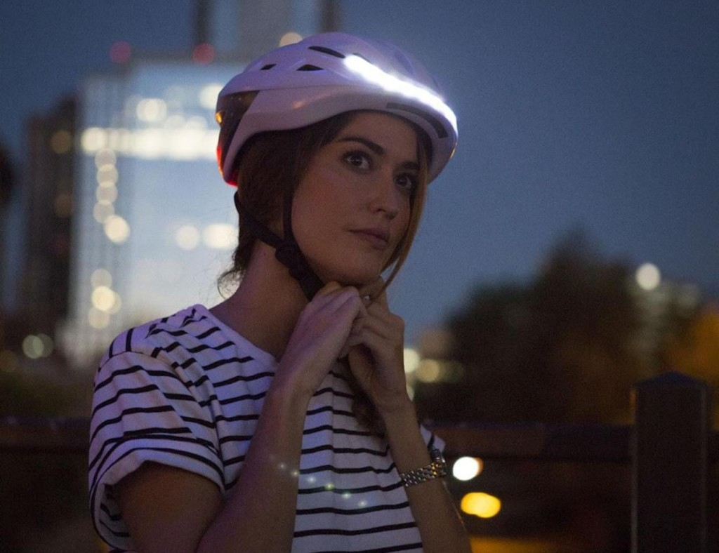 A woman is strapping on a white bike helmet, and the helmet has a white light on the front.
