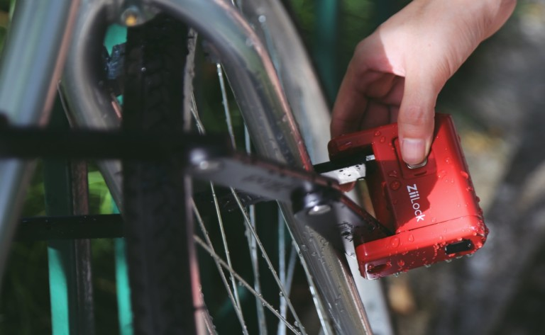 A close up view of a person placing a red bike lock on a bike tire.