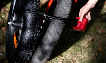 a close up view of a bike tire that has a red and black bike lock attached to it.