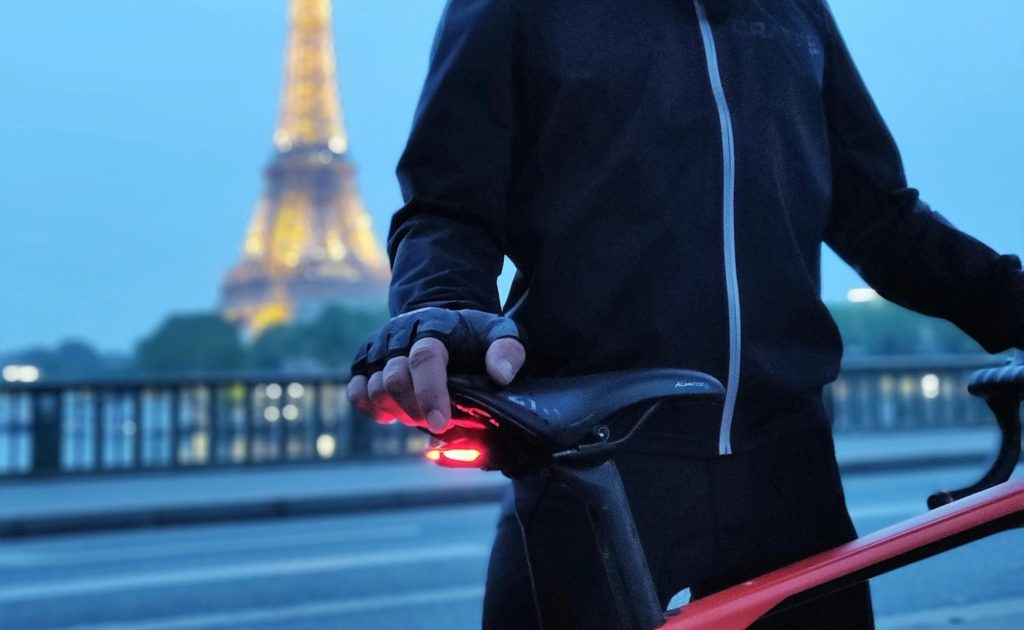 A man is standing next to a bike, and there is a red light under the bike seat.