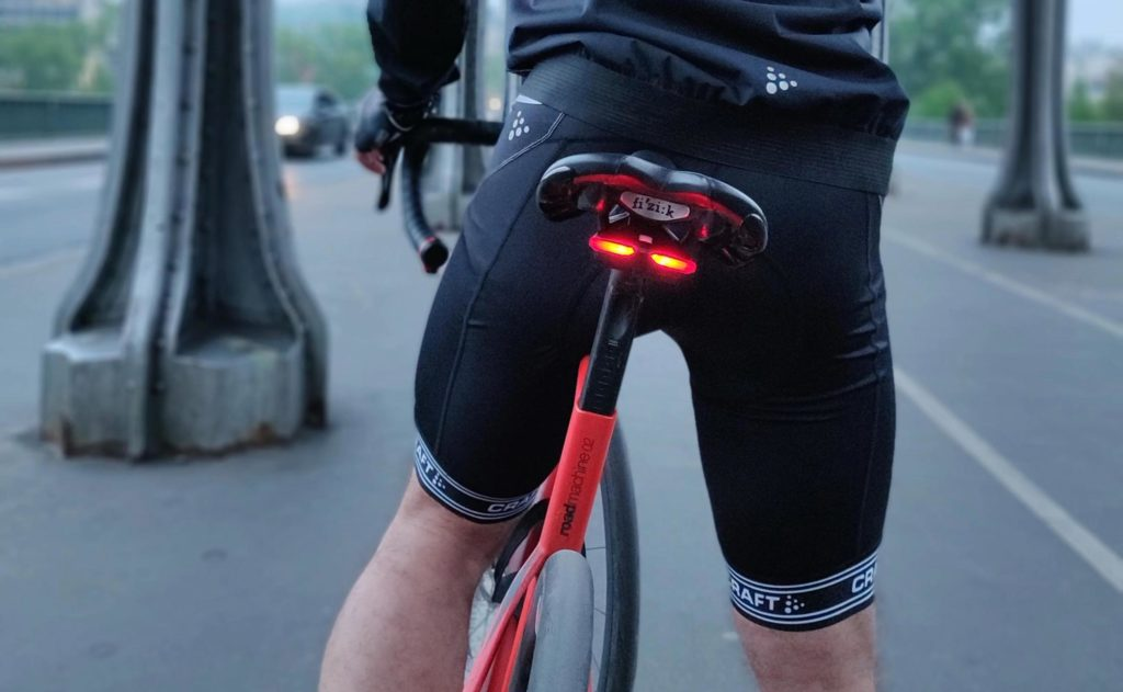 A rear view of a person riding a bike and there is a red light below the bicycle seat.