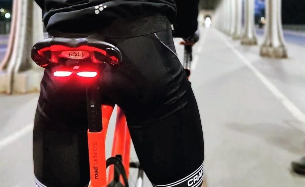 A close-up view of a person riding a bike with a red light below the bike seat