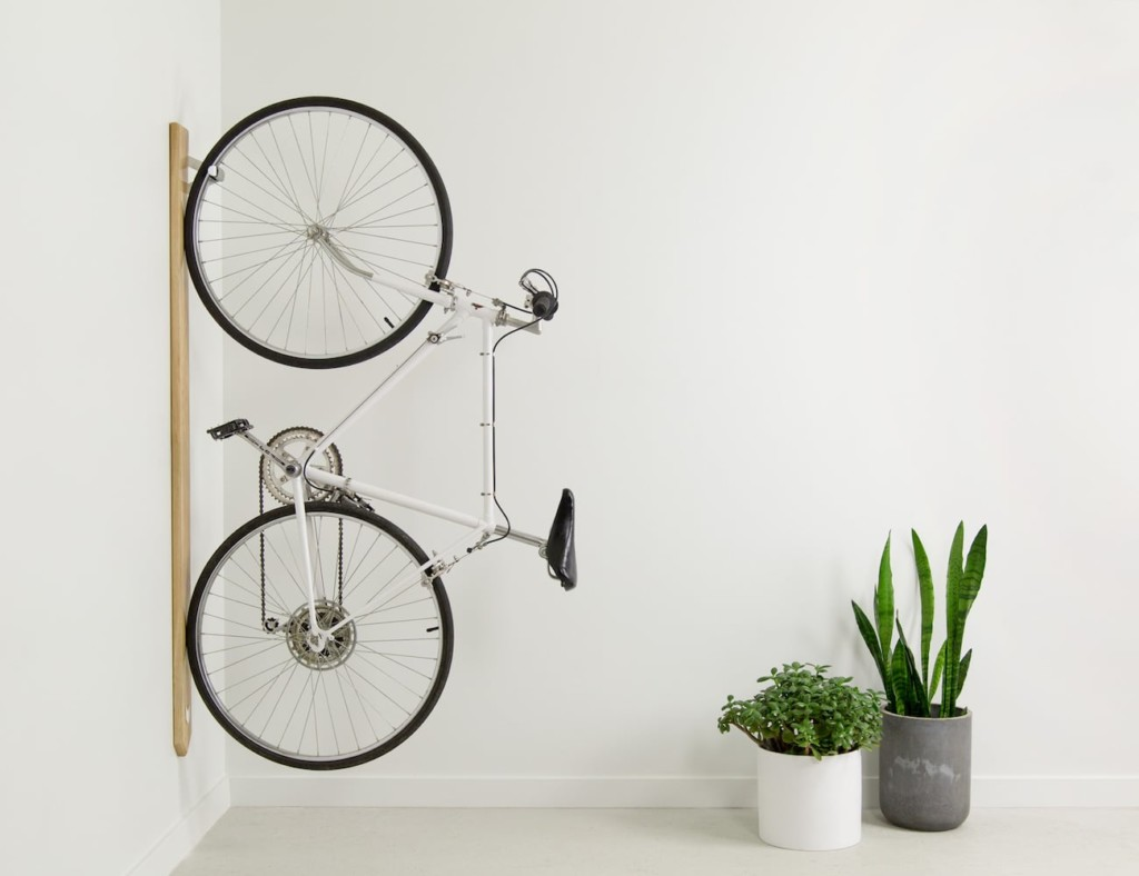 A bicycle hanging vertically on a white wall with two potted plants on the floor.