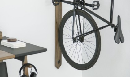 A close-up view of the bottom half of a bicycle hanging vertically on the wall on a bike rack.