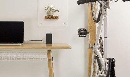 A bike hanging vertically on a white wall next to an office desk.