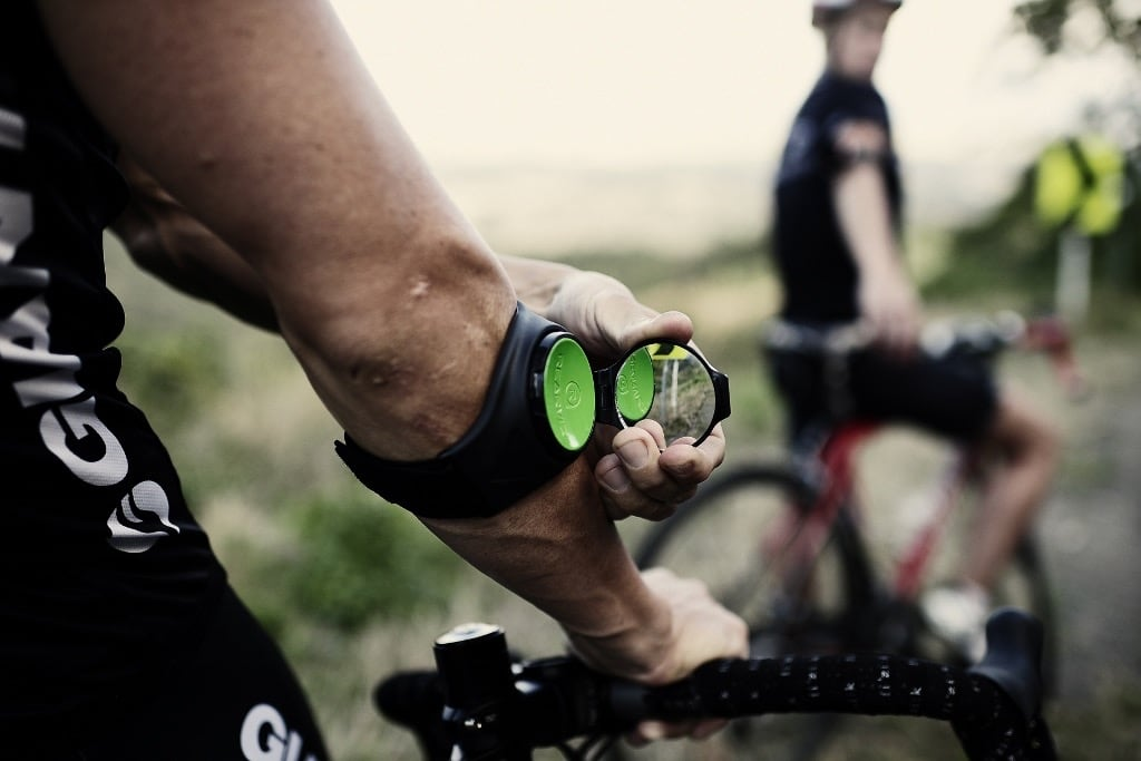A person's hand is on the handlebars of a bike, and there are wearing a rearview mirror gadget on their forearm.