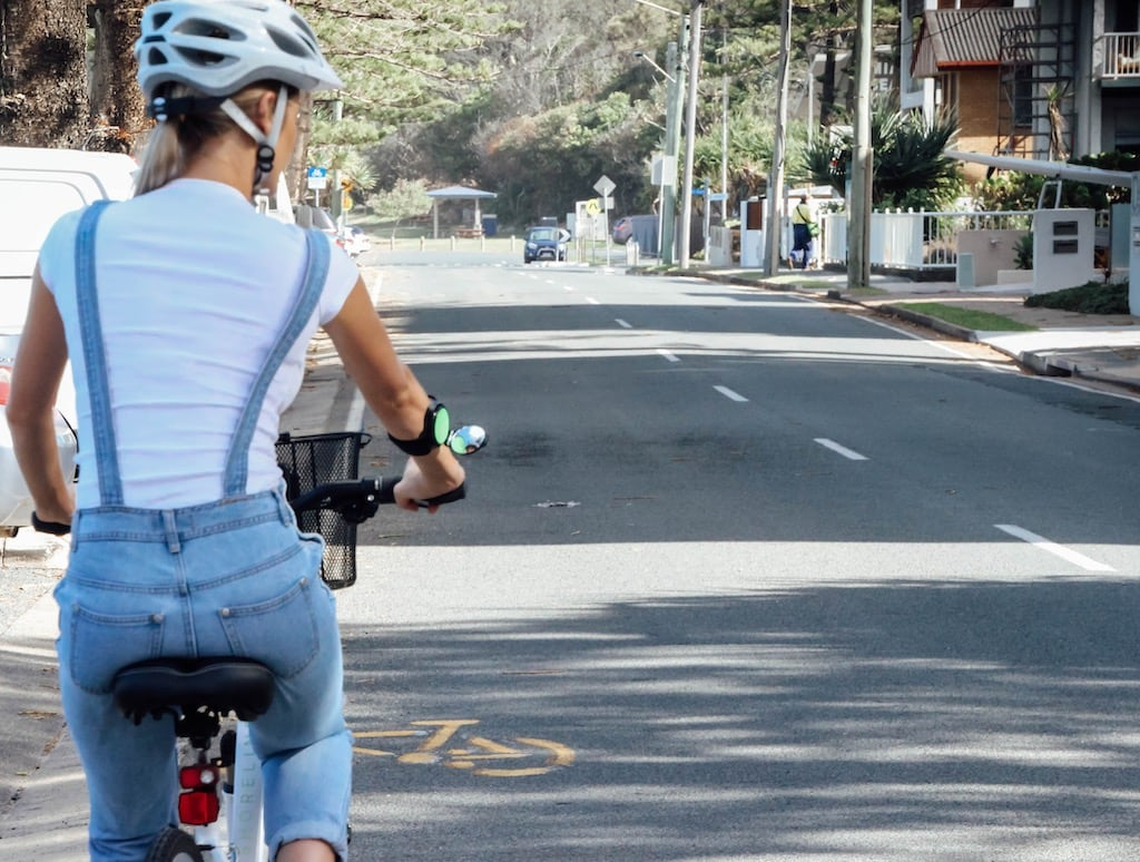 A woman is riding a bicycle on the street and she has a rearview mirror attachment on her forearm