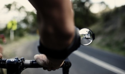 A close up view of a person's arm while they ride their bike, the reflection of a truck in the rearview mirror attachment on their arm.