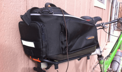 A black bike bag is attached to the back of a bicycle
