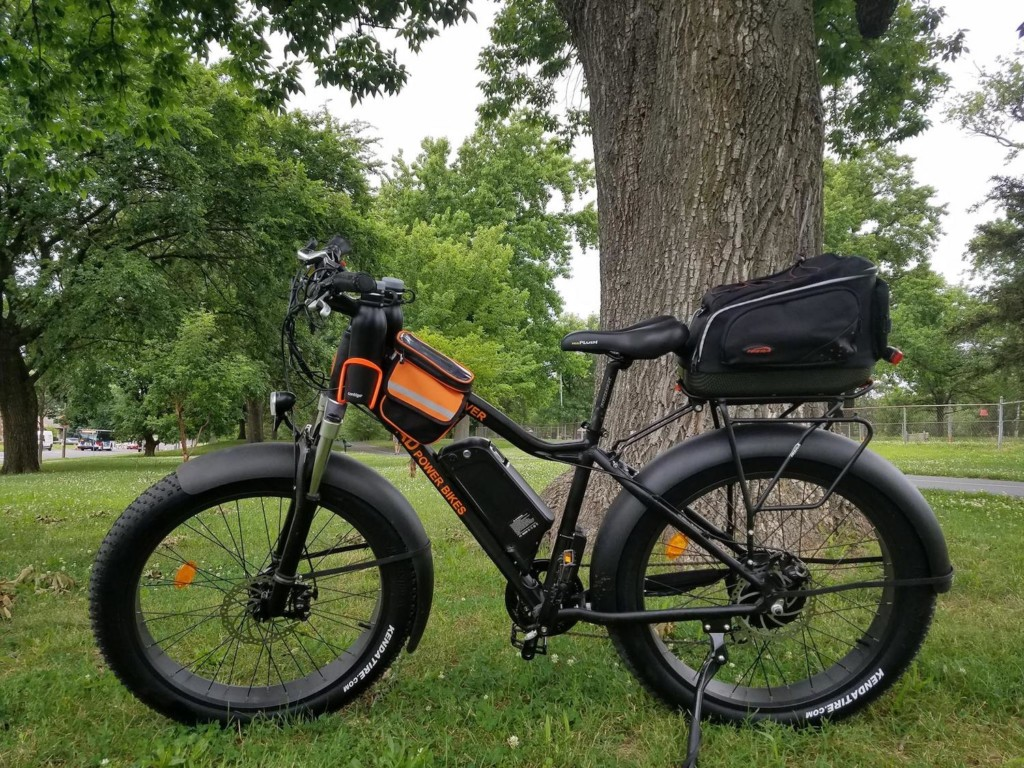A bike against a tree with a trunk bag on the back of it.