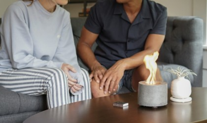 Couple sitting on a couch behind a flame lamp on a coffee table