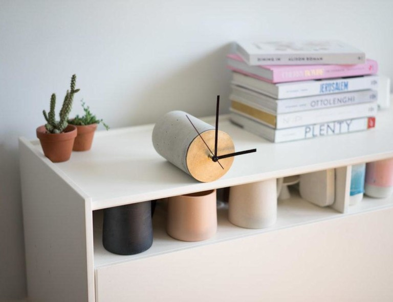Concrete modern clock resting on edge of shelf