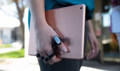 Person wearing wearable keyboard holding laptop