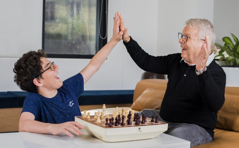 A child and older man play smart board game