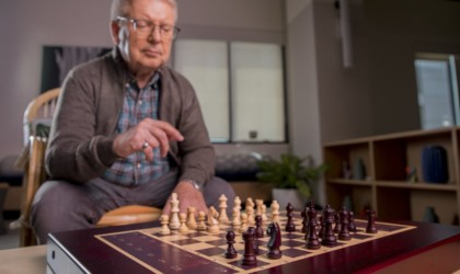 Older board game player playing chess