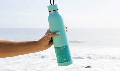 A person's arm holding a water bottle at the beach