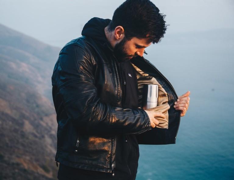 Man in leather jacket putting flask inside pocket