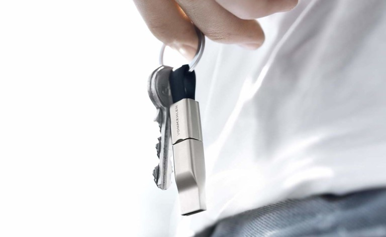 Person holding keys with portable charging cable attached