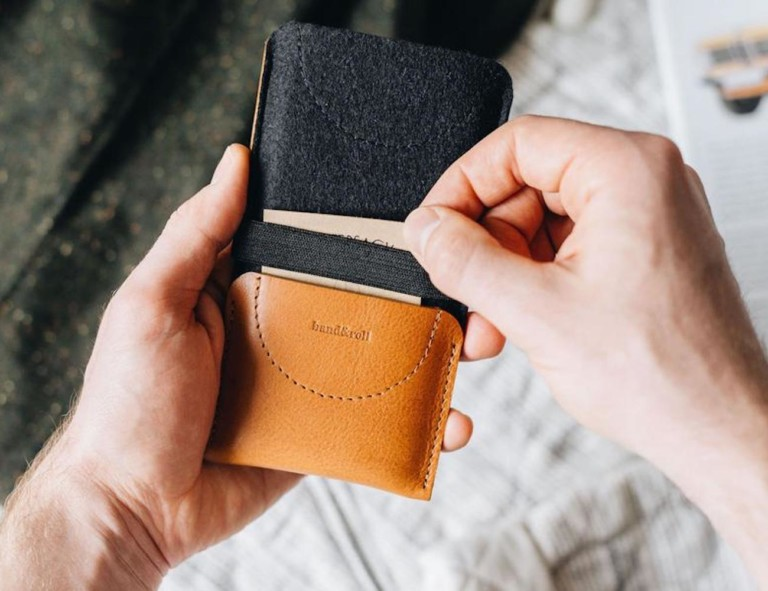 Person pulling card out of wallet phone case