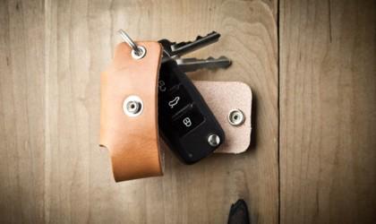 Opened leather key storage pocket on wood surface