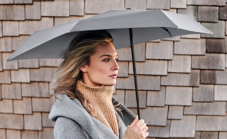Woman holding asymmetrical umbrella