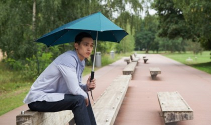 Man sitting with umbrella covering his body