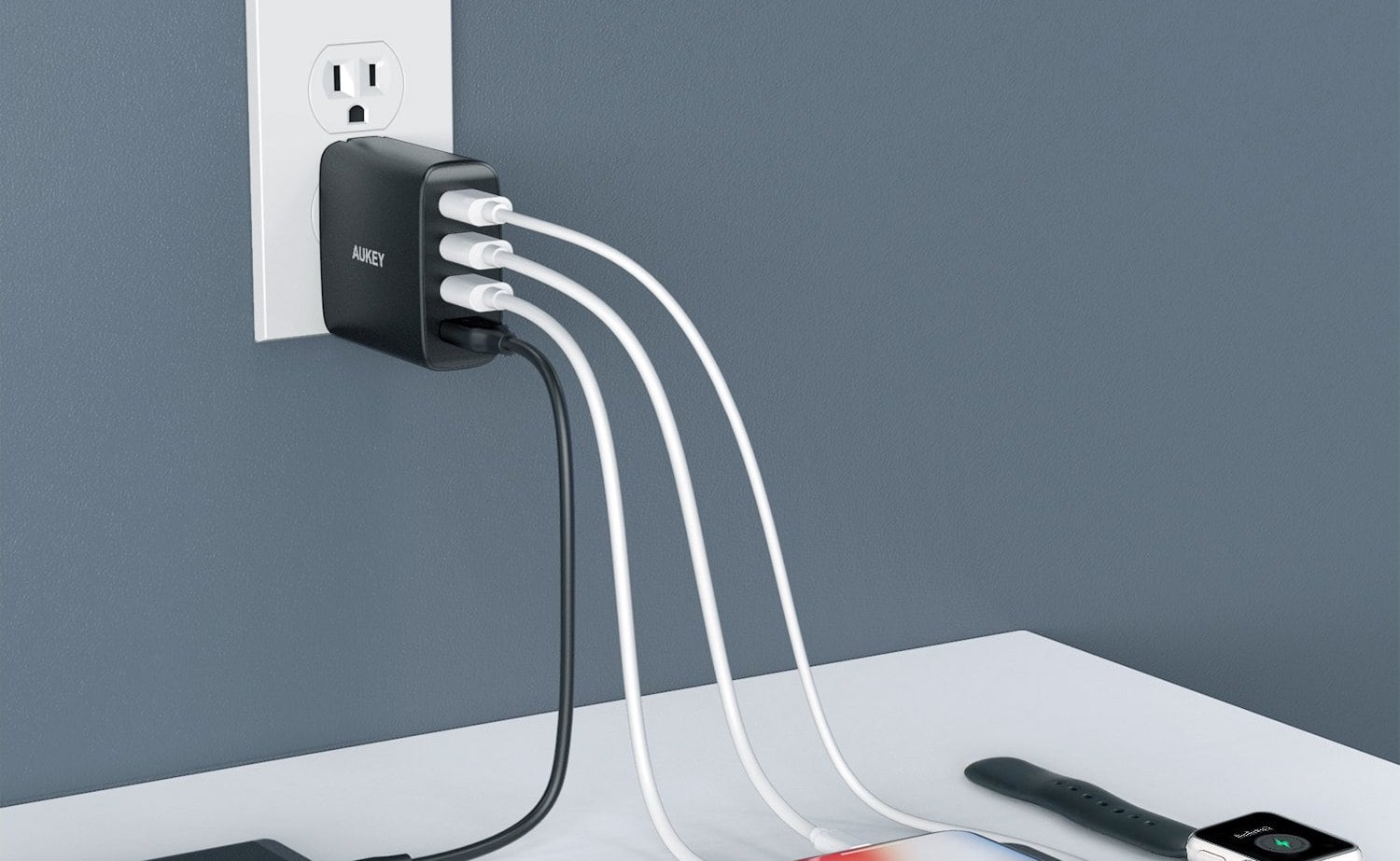 Four-port power adapter plugged into the wall and four devices