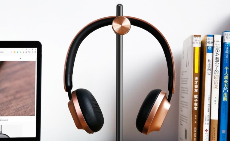 Black and gold headphones hanging on a minimalist headphone stand