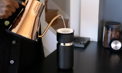 Person making pour-over coffee with travel mug