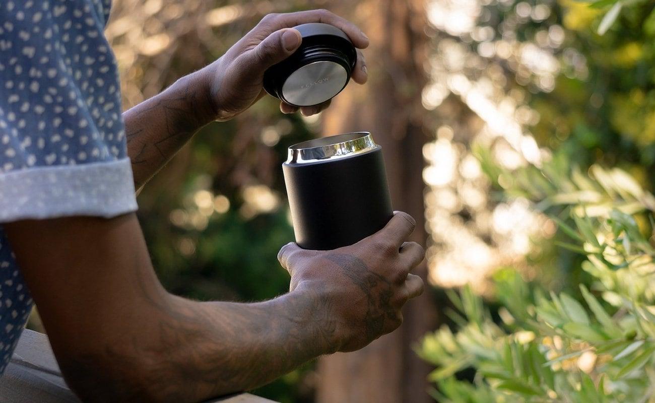 Person putting lid on modern travel mug