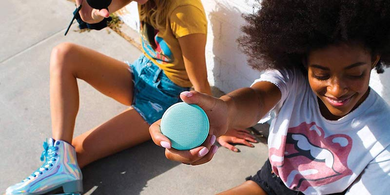 Compact blue speaker held in a girl's hand