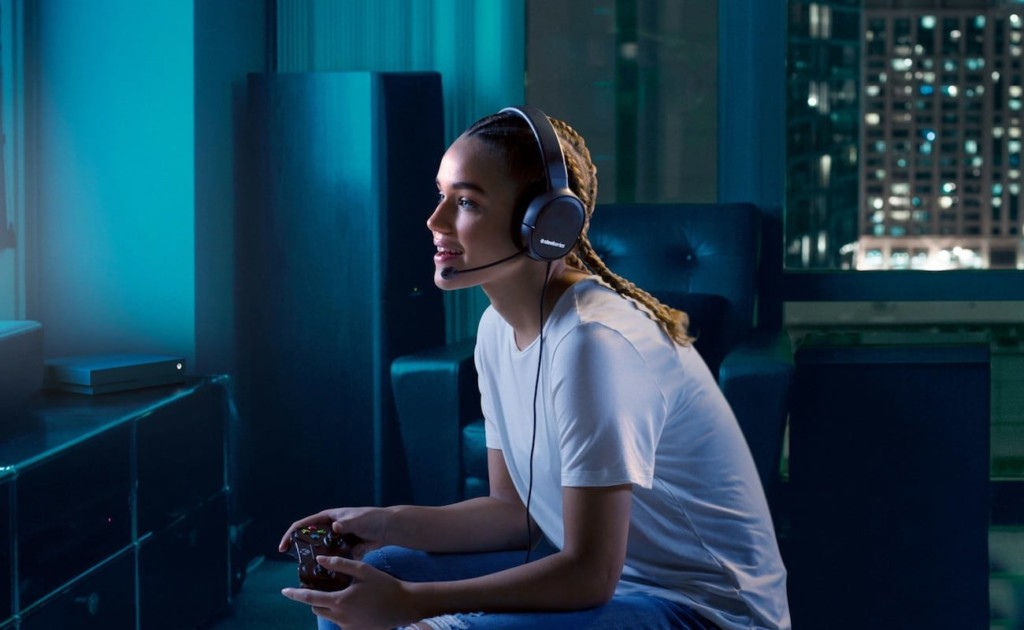 Person in white t-shirt gaming with headset